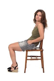 데님 스커트를 입은 여성이 의자에 앉아 흰색 배경의 카메라를 바라보는 모습