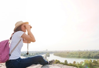 Side view of a woman looking at view through binoculars