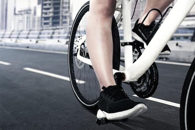 Женщина, едущая на велосипеде по улице, вид сбоку