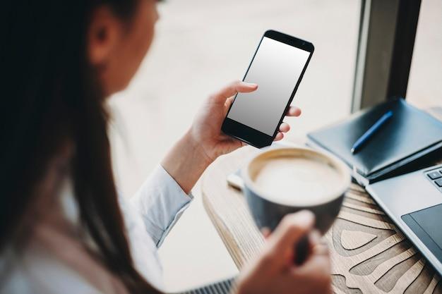 그녀의 손에 커피 한잔과 함께 커피 숍에 앉아있는 여자의 측면보기는 다른 스마트 폰을 사용하는 동안. 온라인 뱅킹 개념.