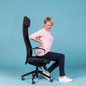 Вид сбоку женщины, сидящей в кресле, страдающем от боли в спине