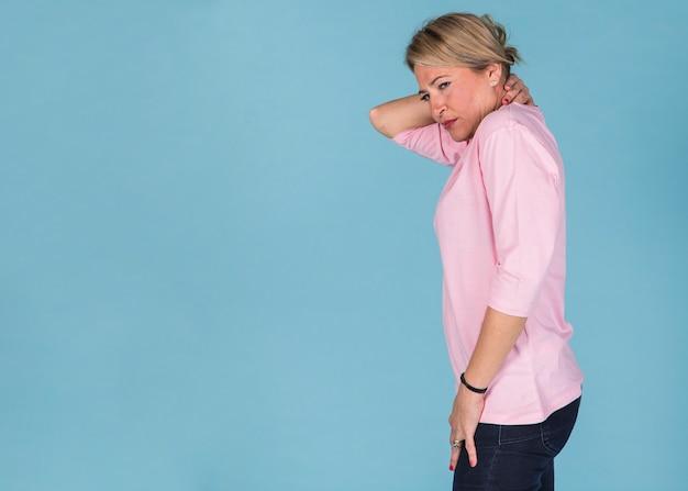 Вид сбоку женщины, страдающей от боли в шее на фоне синих обоев