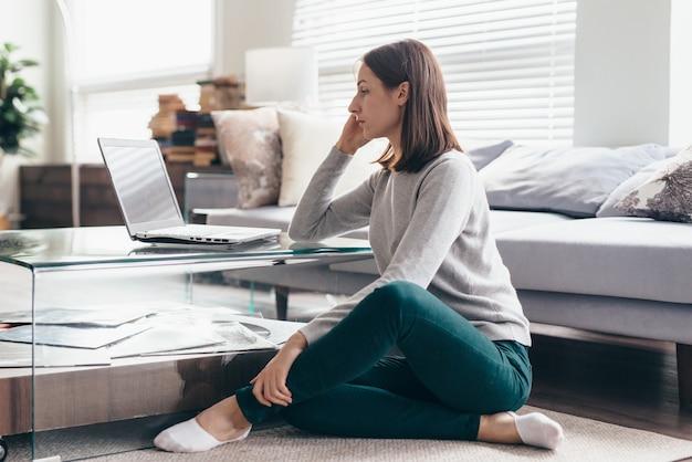 Вид сбоку женщины, работающей на портативном компьютере, сидя у себя дома.