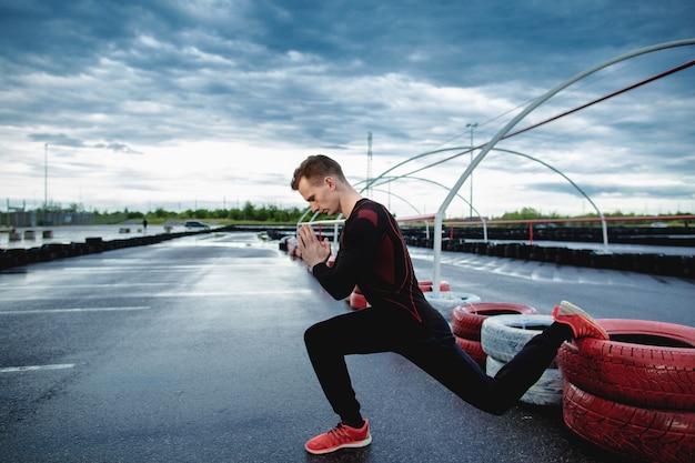 突進を作る運動青年の側面図です。男は屋外で瞑想します。ヨガ、アウトドアスポーツ、トレーニング