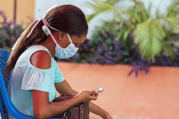 Вид сбоку молодой черной женщины, использующей свой телефон на открытом воздухе