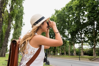 Side view of a young blonde woman wearing hat taking photograph on camera