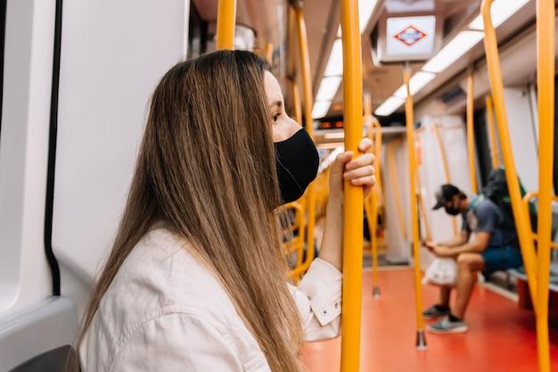 마드리드의 도시에서 지하철 차량 안에 앉아 얼굴 마스크와 젊은 금발의 여자의 측면보기.