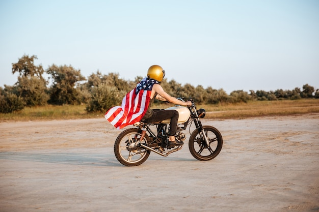 Вид сбоку на молодого брутального человека в золотом шлеме и мысе с американским флагом за рулем ретро-мотоцикла