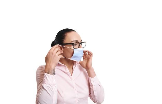 Вид сбоку молодой деловой женщины, надевающей медицинскую защитную маску.