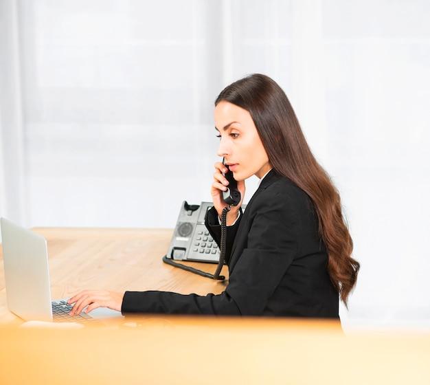 Взгляд со стороны молодой коммерсантки используя компьтер-книжку пока говорящ на телефоне в офисе