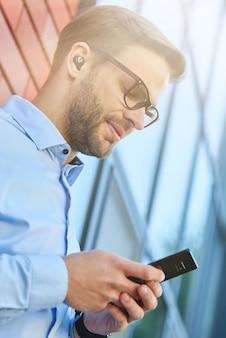 スマートフォンを使用してワイヤレスイヤホンを身に着けている若いハンサムなビジネスマンの側面図