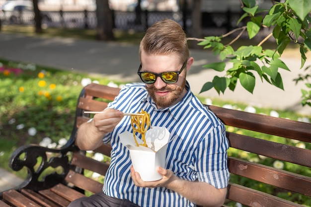 에 앉아있는 동안 도시락에서 중국 국수를 먹는 젊은 잘 생긴 힙 스터 남자의 측면보기는