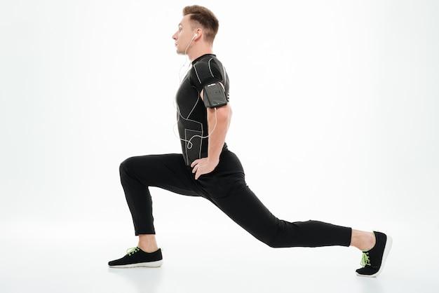 足を伸ばして若い健康的なスポーツマンの側面図