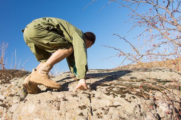 水色の空を背景に熱帯気候のフィールドで大きな岩を登る若い男性スカウトの側面図。