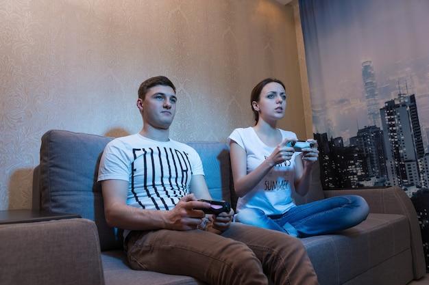게임의 과정에 열정을 갖고 집에서 함께 소파에 앉아 비디오 게임을 하는 젊은 남녀의 옆모습