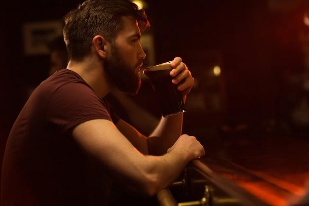 ビールのグラスを飲む若い男の側面図