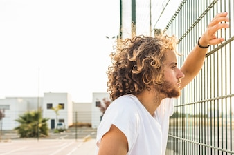 Side view of a young man looking through fence