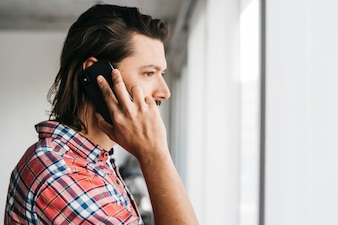 Side view of a young man talking on mobile phone