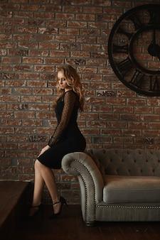 내부에서 포즈를 취하는 짧은 검은 드레스에 슬림 바디와 젊은 모델 여자의 측면보기