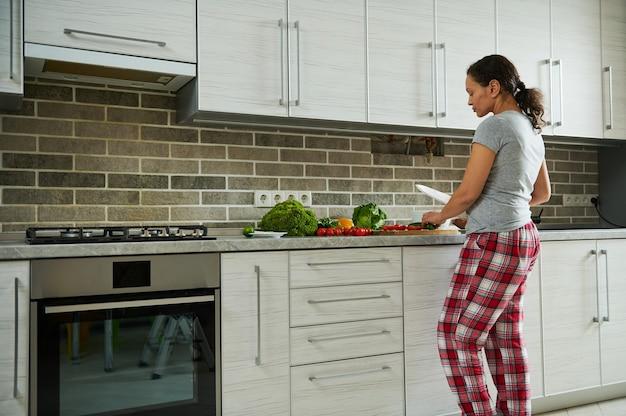 집에서 요리하는 젊은 여자의 측면보기.