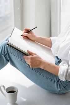 Вид сбоку молодой женщины, рисующей дома у окна