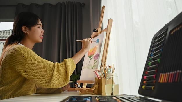 若い女性の側面図は、アートワークショップで花の帆布を描いています