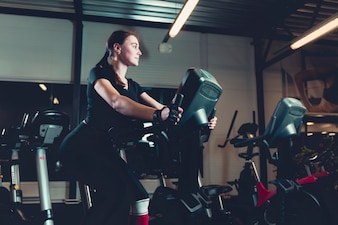 Side view of a young woman riding on exercise bike in gym