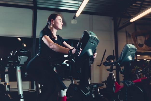 Вид сбоку молодая женщина, верхом на велотренажер в тренажерном зале