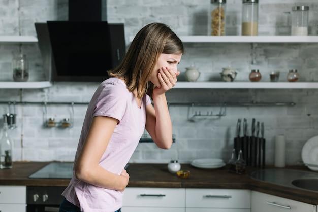 Боковой вид молодой женщины, страдающей тошнотой на кухне