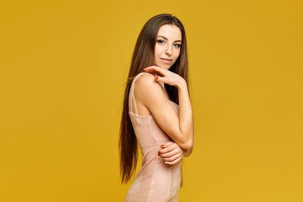 黄色の背景にベージュのドレスを着た優しい化粧の若い女性の側面図。