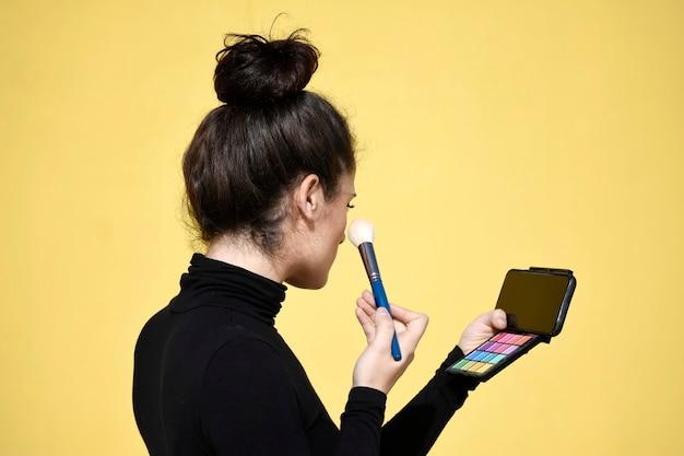 Вид сбоку молодой женщины с хвостиком, использующей телефон как зеркало при нанесении кисти для макияжа на кожу лица