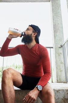 Вид сбоку активного бородатого спортсмена, пьющего воду из стеклянной бутылки во время отдыха и сидя на лестнице в яркий день.