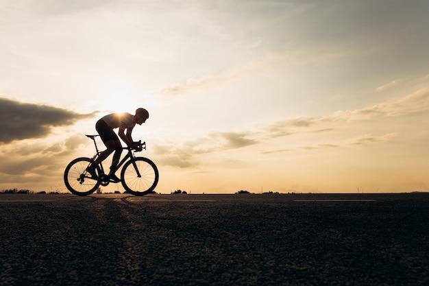 일몰 동안 자연 사이에서 보호 헬멧 승마 자전거에 적극적인 스포츠맨의 측면보기