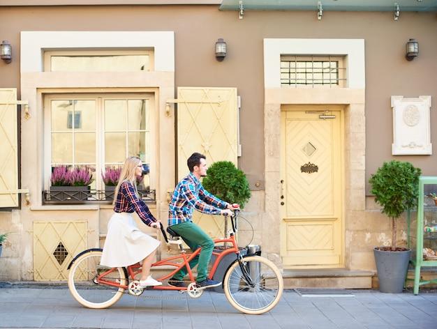 Взгляд со стороны активной туристической пары, бородатого человека и белокурой женщины задействуя тандем велосипед вдоль пустого вымощенного тротуара на яркий солнечный летний день городскими жилыми домами.