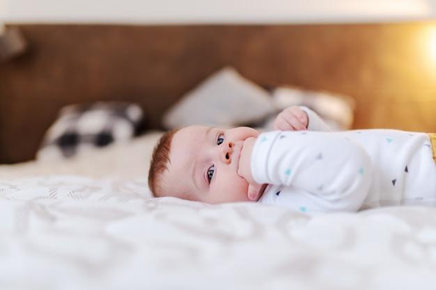Взгляд со стороны прелестного кавказского ребёнка лежа в кровати и всасывая пальцы.