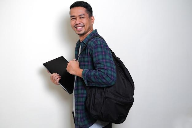Взрослый азиатский мужчина, вид сбоку, приносит рюкзак и ноутбук, показывая счастливое выражение лица