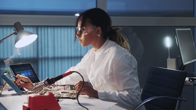 실험실에서 멀티 미터 테스터 및 기타 전자 기기를 사용하는 아프리카 계 미국인 전자 전문가의 측면보기