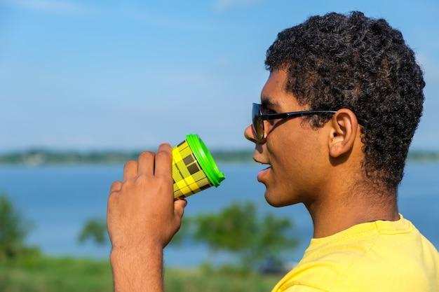 여름에 강가에서 야외에서 커피 맛을 즐기는 선글라스를 쓴 아프리카계 미국인 남자의 측면. 클로즈업 보기