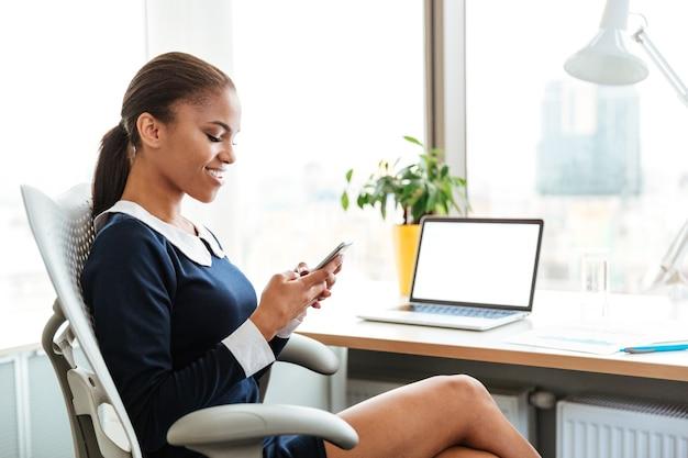 電話でテーブルのそばに座っているアフリカのビジネス女性の側面図
