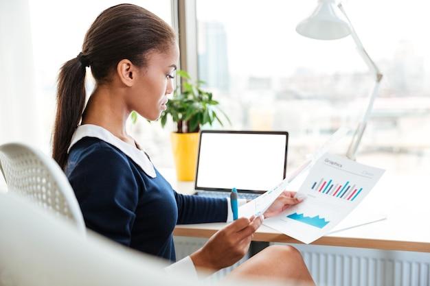 オフィスのテーブルのそばに座って、書類を保持しているドレスを着たアフリカのビジネス女性の側面図