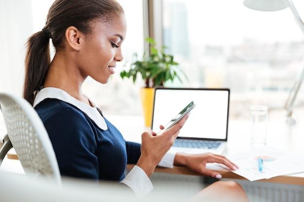 オフィスの窓の近くのテーブルのそばに座って電話を見ているドレスを着たアフリカのビジネス女性の側面図
