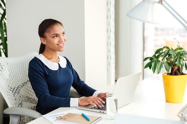 窓の近くのラップトップで職場に座っているドレスを着たアフリカのビジネス女性の側面図