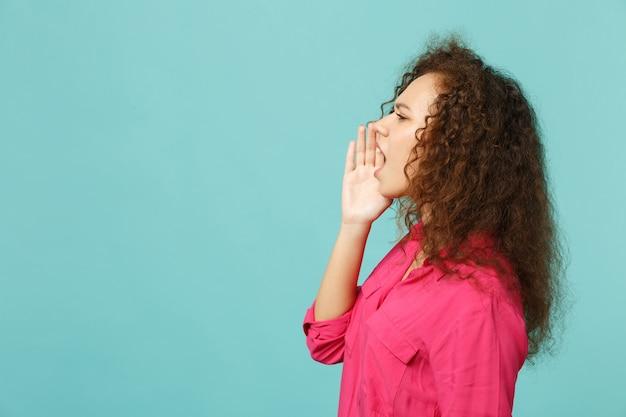 スタジオの青いターコイズブルーの壁の背景に分離された口の近くで手のジェスチャーで叫んでカジュアルな服を着たアフリカの女の子の側面図。人々の誠実な感情、ライフスタイルのコンセプト。コピースペースをモックアップします。