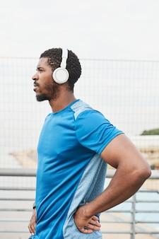 屋外でのトレーニング中に音楽を聴いているワイヤレスヘッドフォンでアフリカの若いアスリートの側面図