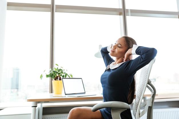 窓の近くのテーブルのそばに座って、オフィスでストレッチドレスを着たアフロビジネス女性の側面図