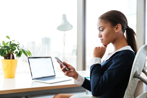 電話とラップトップで窓の近くのテーブルのそばに座っているドレスを着たアフロビジネス女性の側面図