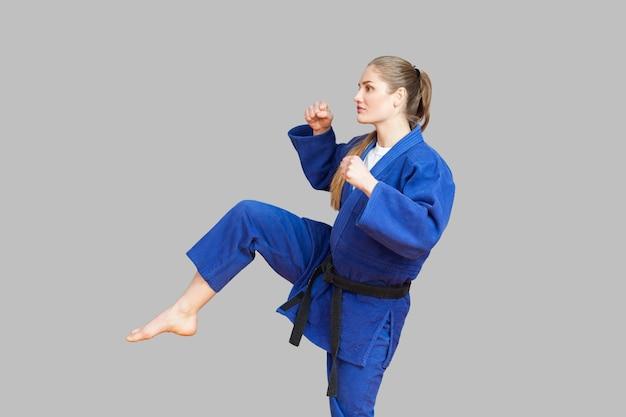 黒帯の青い着物を着た攻撃的な運動空手の女性の側面図は、足でパンチし、目をそらして戦う準備ができています。日本の武道の概念。屋内、スタジオショット、灰色の背景