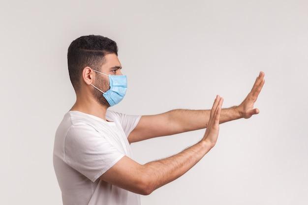 Covid-19感染を恐れて、衛生的な保護マスクのジェスチャー停止で警戒する男性の側面図