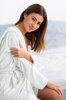Очаровательная женщина позирует в халате, вид сбоку