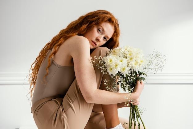 앉아서 봄 꽃과 함께 포즈를 취하는 매혹적인 여자의 측면보기